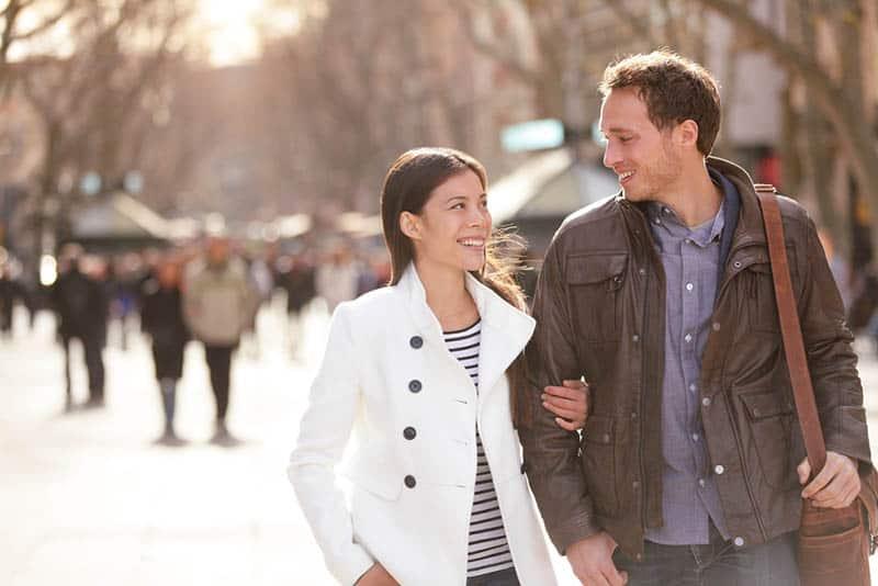 lächelnde Frau, die einen Mann hält und einander beim Gehen auf der Straße schaut