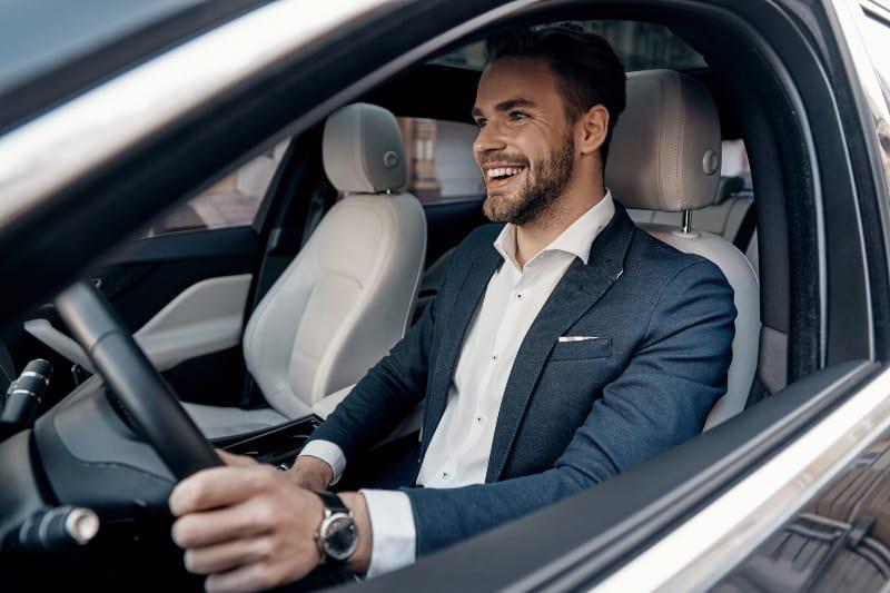 lächelnder Mann im Anzug, der Auto fährt