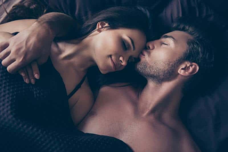 schönes Paar, sie umarmen sich unter der Decke im Bett