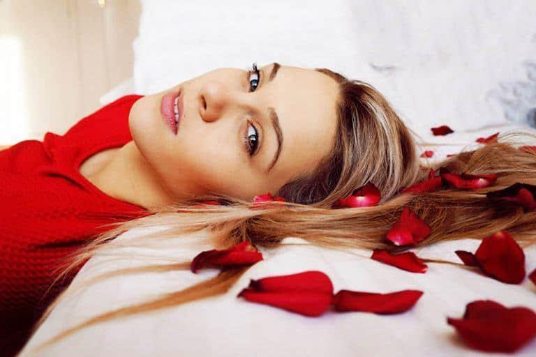 Das Mädchen liegt auf einem Bett mit Rosenblättern
