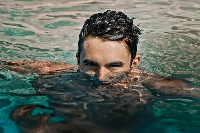 ein junger Mann, der in einem Pool schwimmt