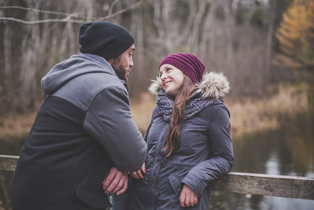 Auf einer Holzbrücke im Herbst spricht ein Liebespaar