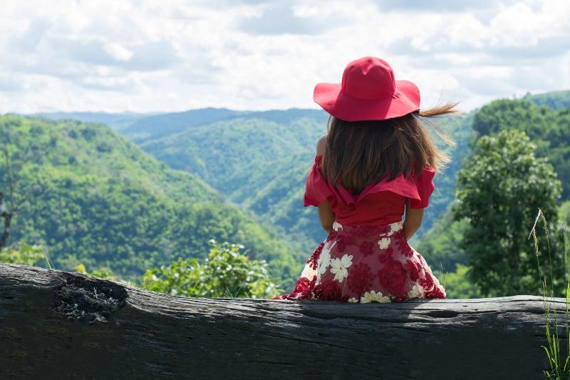 Das Mädchen sitzt allein in einem Kleid auf dem Berg