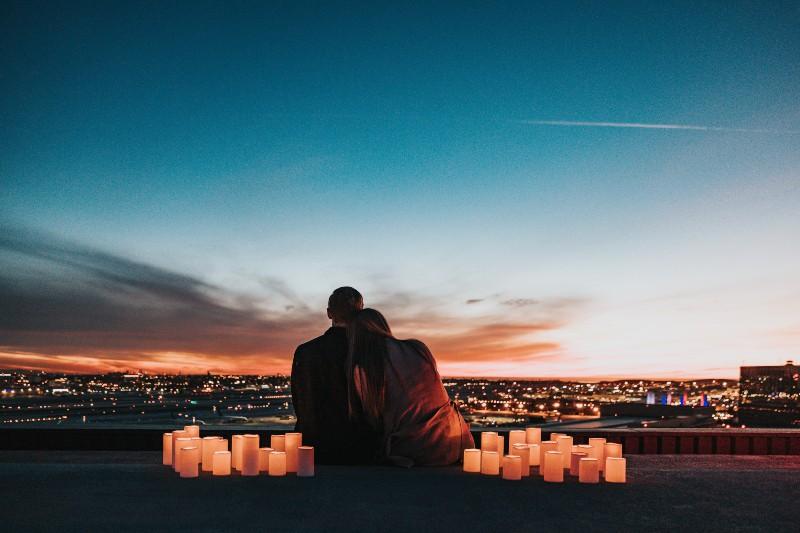 Das Paar sitzt auf einem von Kerzen umgebenen Gebäude