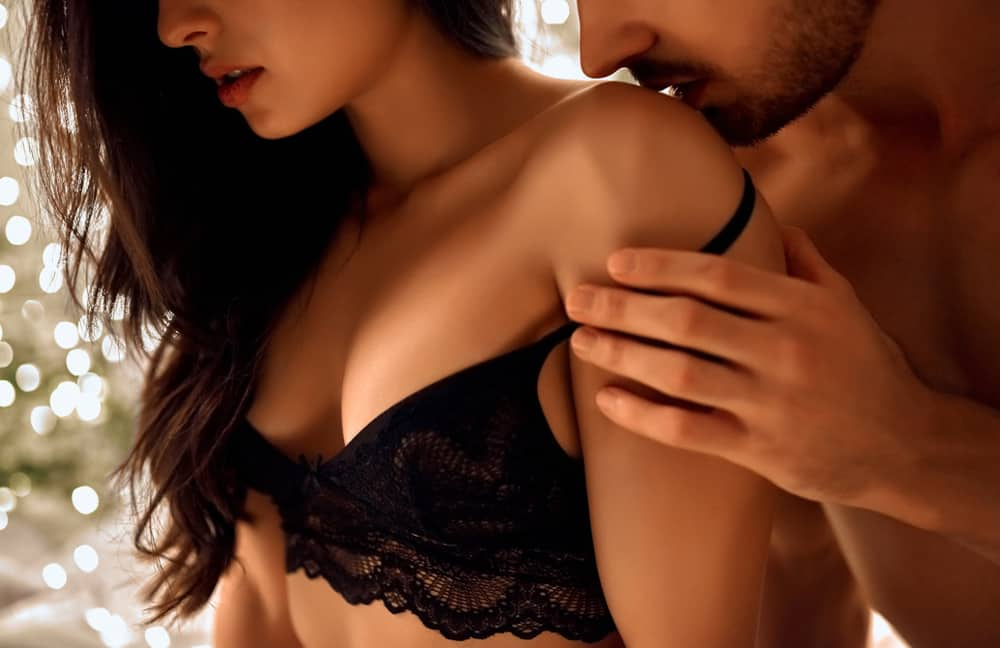 Der Mann im Rücken küsst die Frau sanft und zieht ihren BH aus