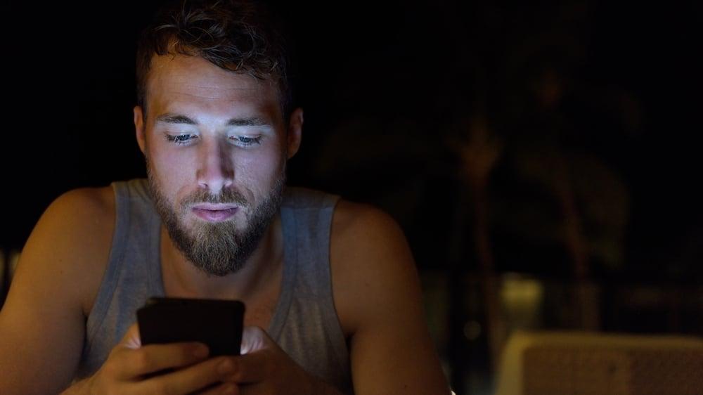 Der Mann im Unterhemd schreibt SMS sorgfältig