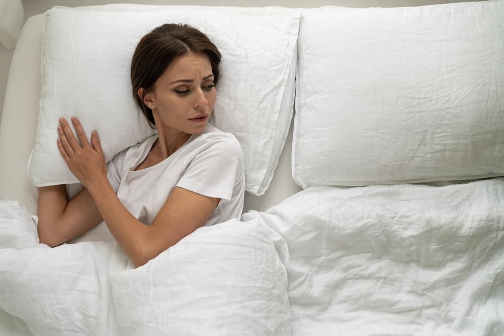 Die Frau liegt traurig im Bett