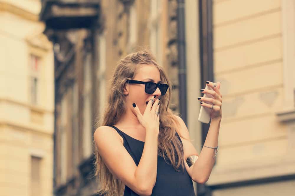 Die attraktive Blondine schaut überrascht auf ihr Handy