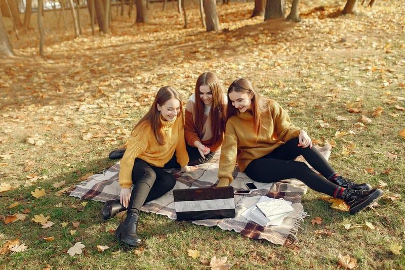 Drei junge Frauen sitzen auf Decken im Park