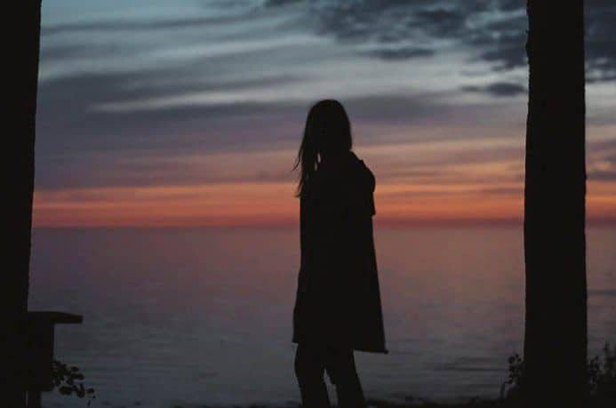 ein einsames Mädchen mit Blick auf das Meer
