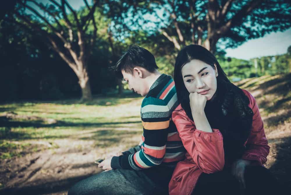 Ein Mann am Telefon und eine traurige Frau sitzen im Park