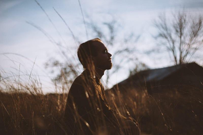 Ein Mann auf einem Grasfeld meditiert