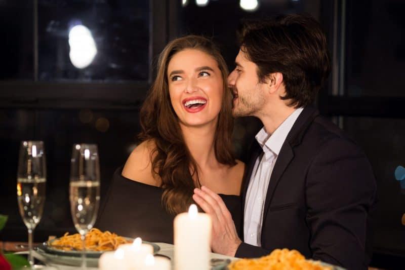 Ein Mann beim Abendessen im Restaurant flüstert einer lächelnden Frau etwas ins Ohr