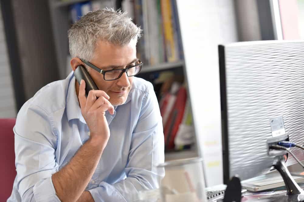 Ein Mann im Büro sitzt und telefoniert