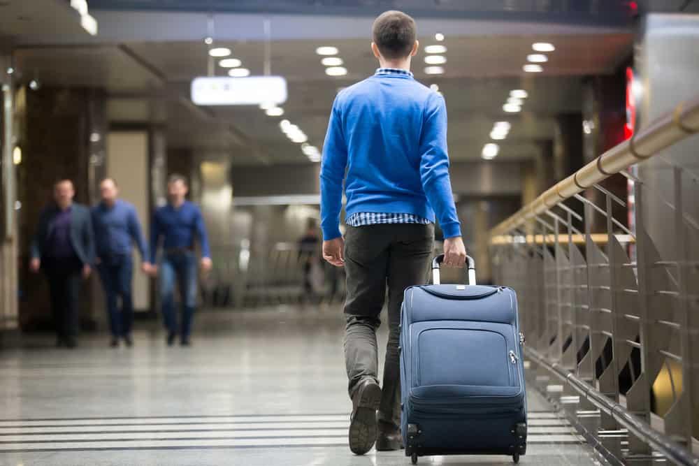 Ein Mann in einem blauen Pullover zieht am Flughafen einen Koffer