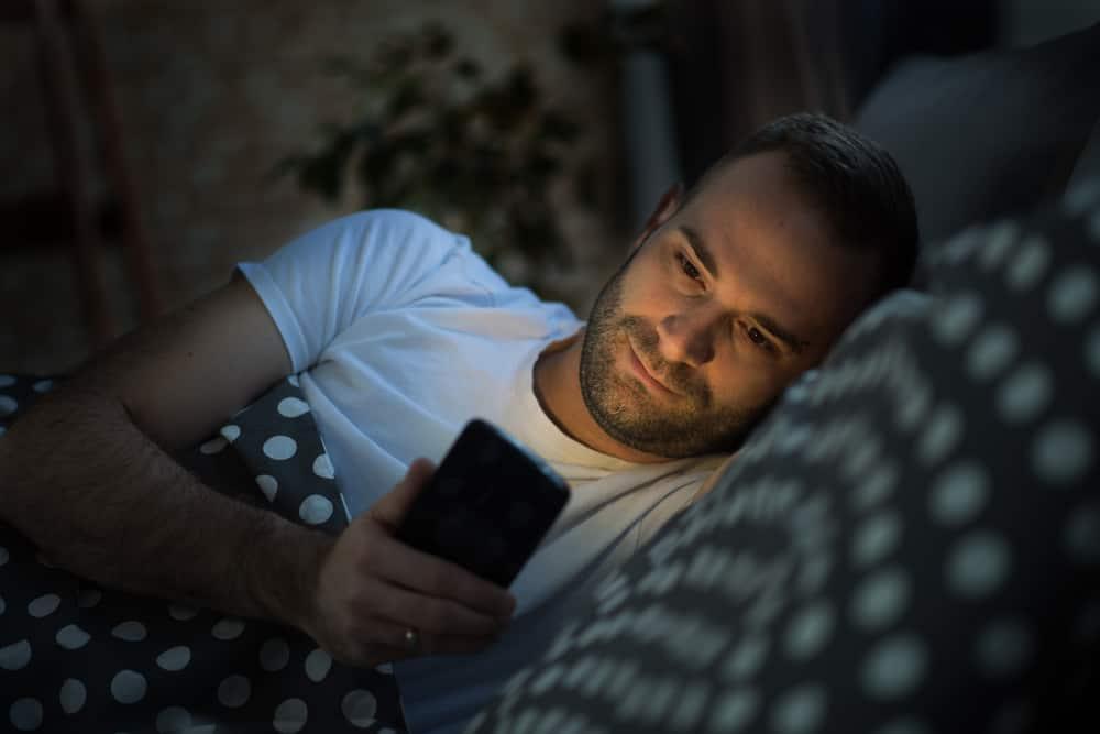 Ein Mann liegt auf dem Bett und schreibt eine Nachricht auf sein Handy