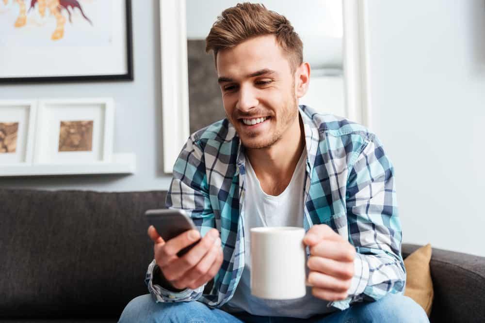 Ein Mann mit Kaffee schaut auf sein Handy