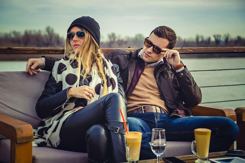 Ein Mann sieht trotzig eine attraktive Frau an, mit der er auf der Terrasse eines Cafés sitzt