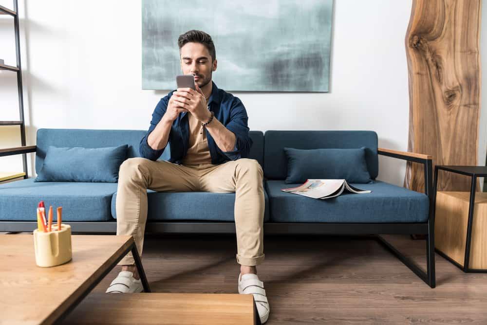 Ein Mann sitzt auf der Couch und schreibt eine SMS