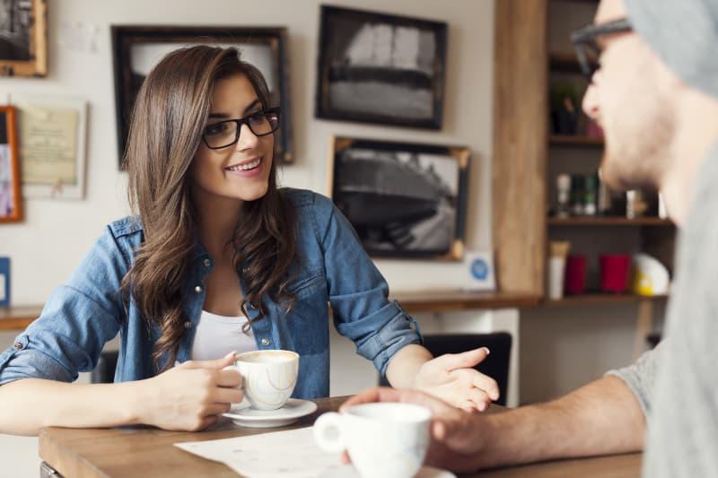 Ein Mann und eine Frau unterhalten sich in einer Cafeteria