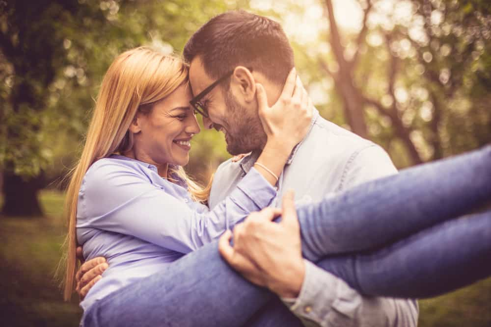 Ein glücklicher Mann im Park hält eine verliebte Frau in den Armen