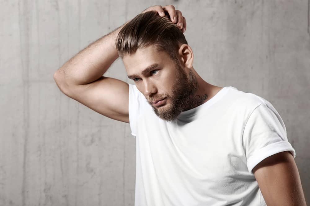 Ein gutaussehender Mann mit Bart steht auf und hält den Kopf