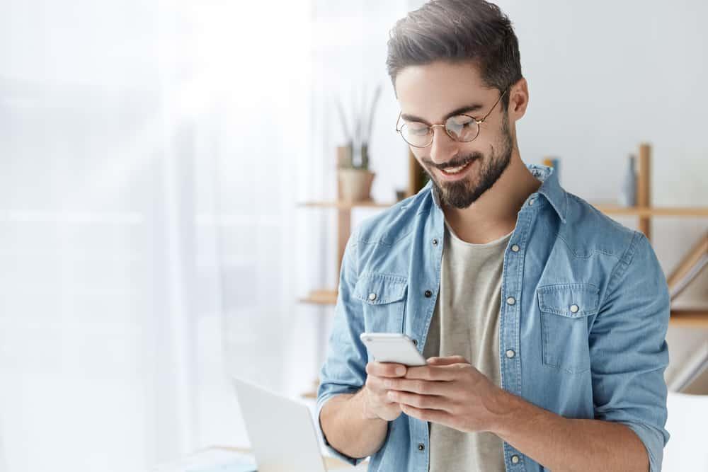 Ein lächelnder Mann in einem Jeanshemd schreibt eine SMS