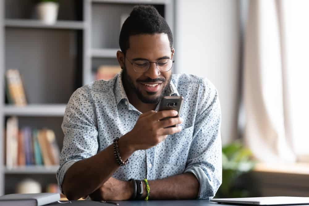 Ein lächelnder schwarzer Mann mit Brille schreibt eine SMS