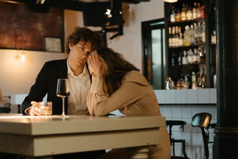 Ein wütender Mann beschuldigt eine Frau für etwas, das sie beim Sitzen in einem Café am Kopf hält