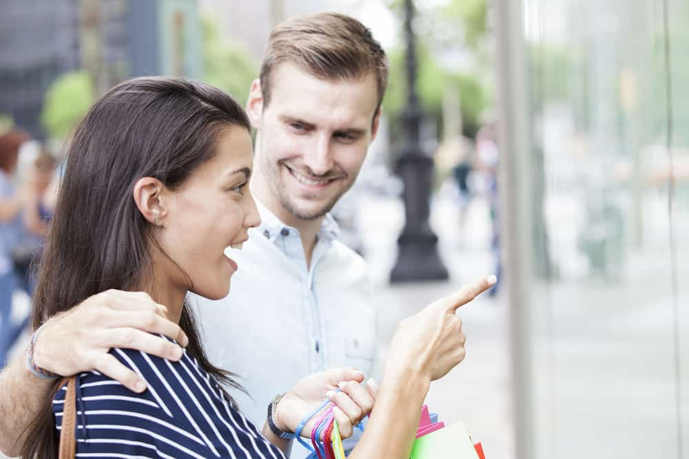 Eine Frau beim Einkaufen zeigt mit dem Finger auf etwas für ihren Mann