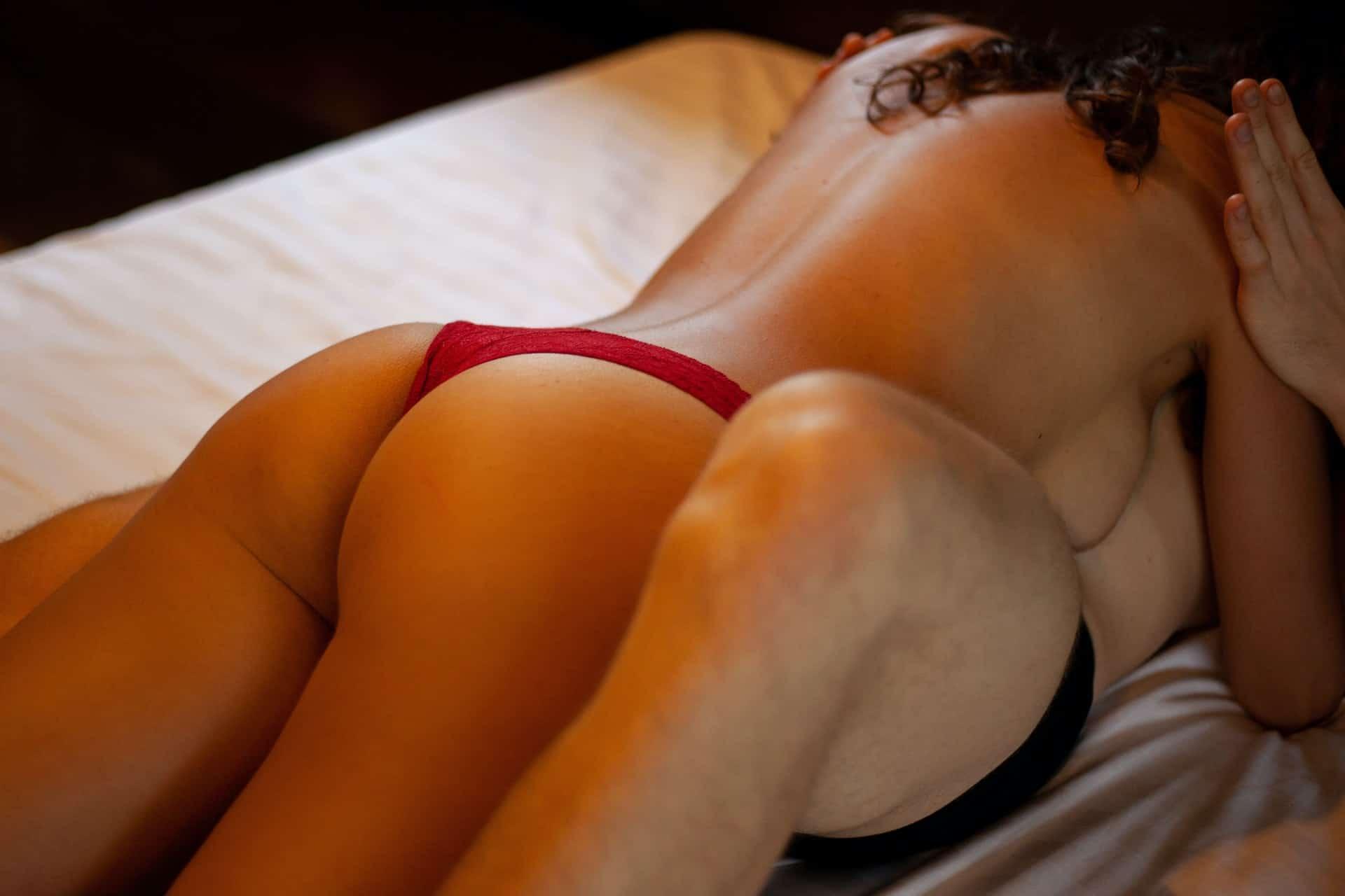 Eine Frau in einem roten Tanga liegt auf einem Mann im Bett