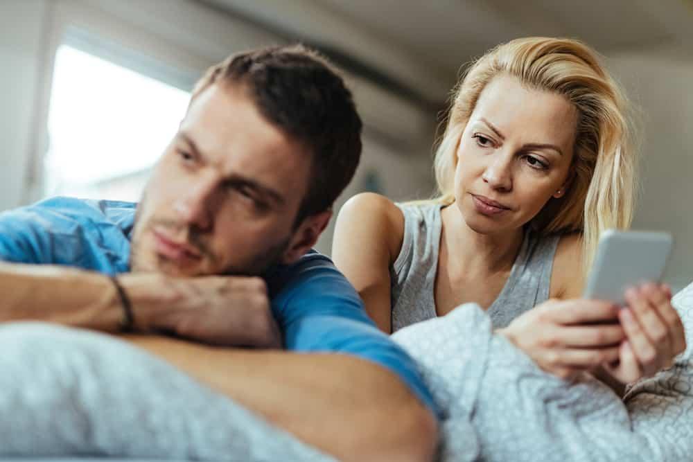 Eine Frau mit einem Telefon sieht ihren Mann an, der sie ignoriert