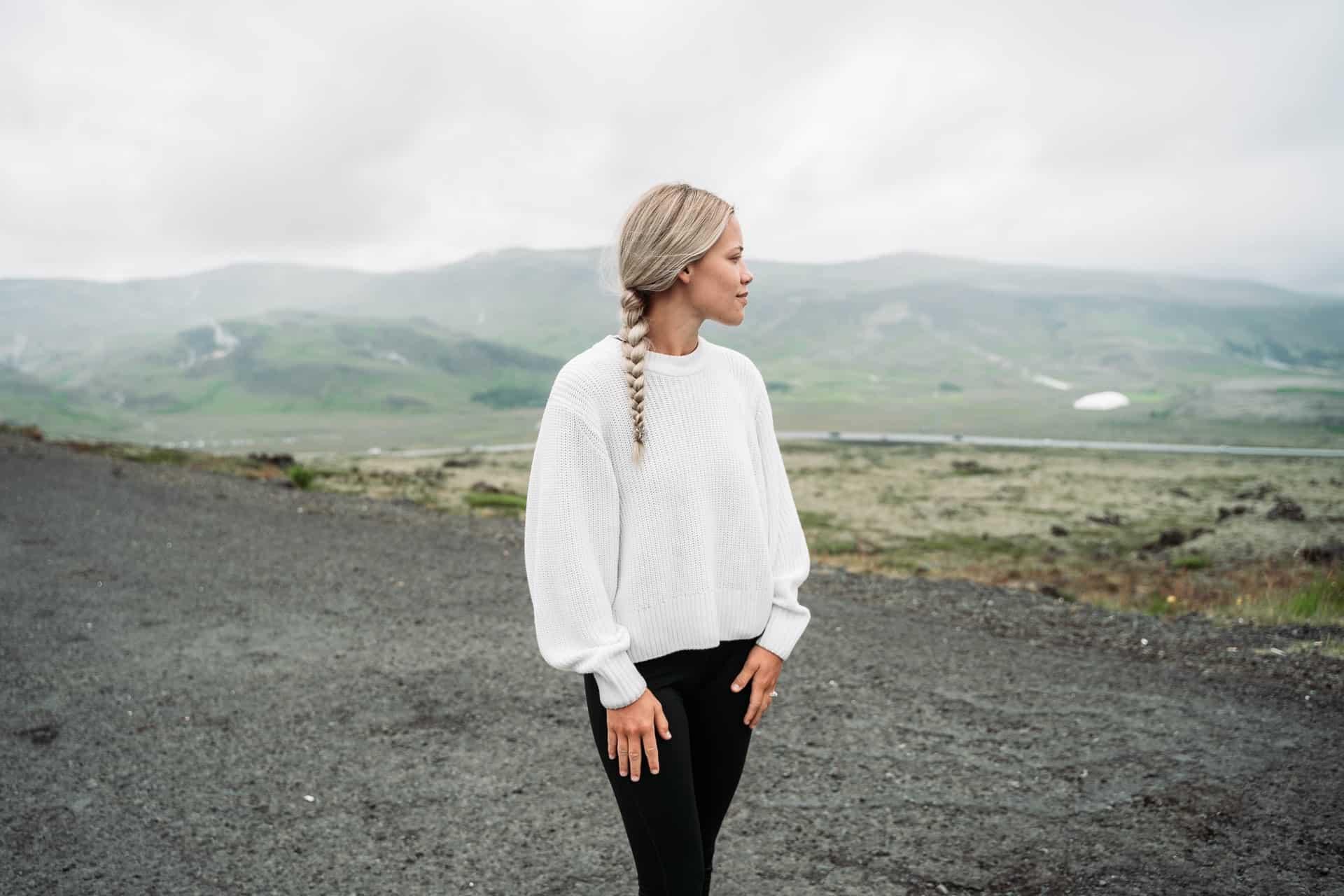 Eine Frau mit einem Zopf steht auf und schaut in die Ferne