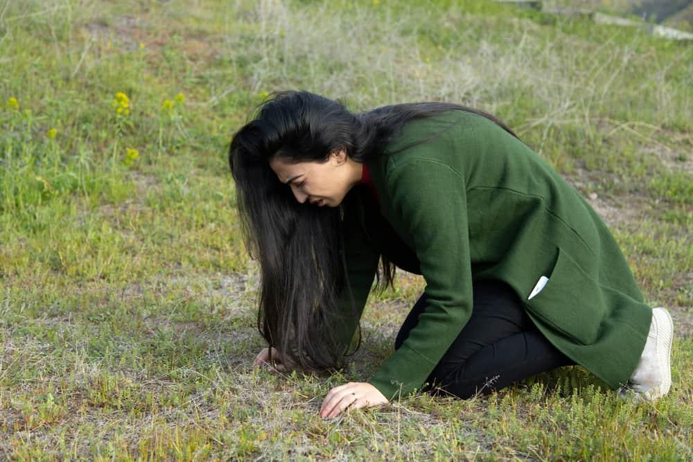 Eine depressive Frau kniet auf einer Wiese