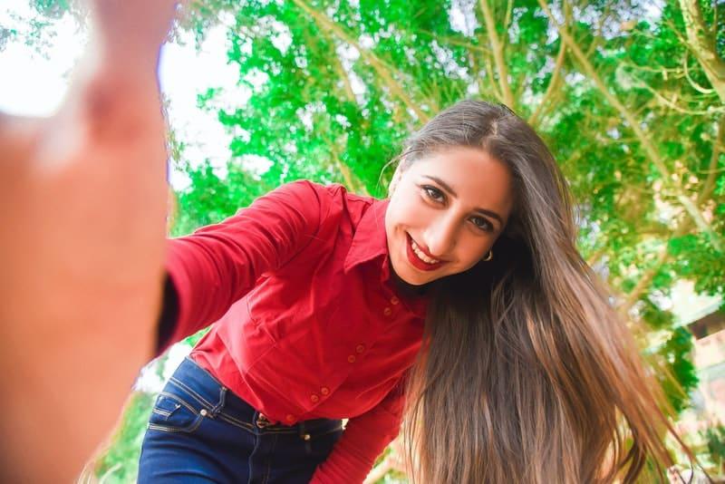 Eine lächelnde junge Frau in einem roten Hemd macht ein Selfie-Foto