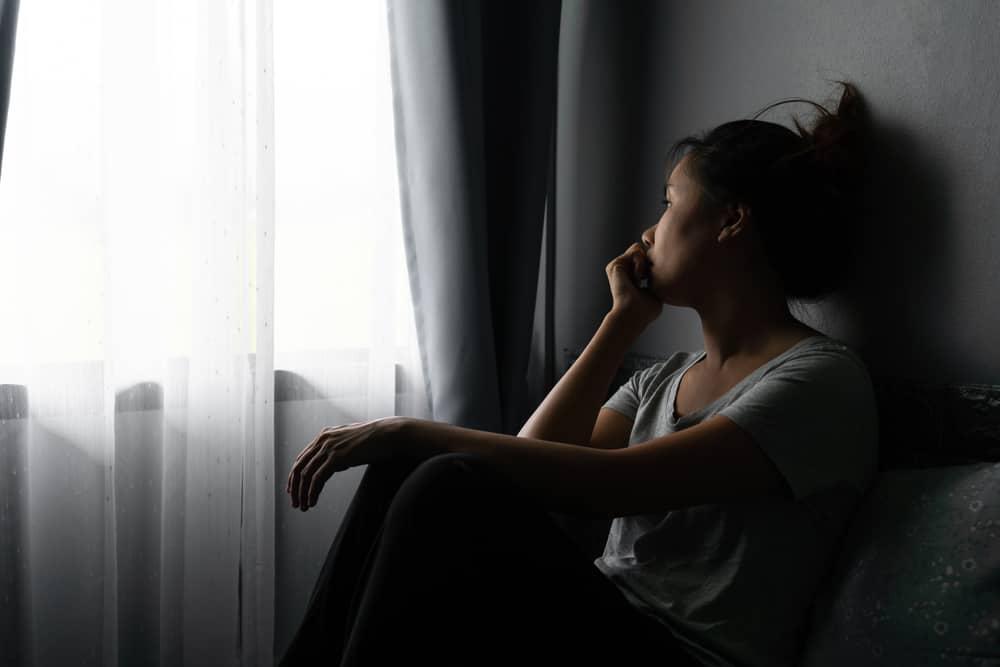 Eine traurige Asiatin sitzt am Fenster und denkt nach