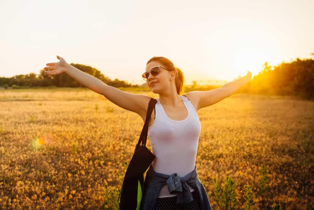 Eine zufriedene Frau steht mit ausgestreckten Armen auf einem Grasfeld