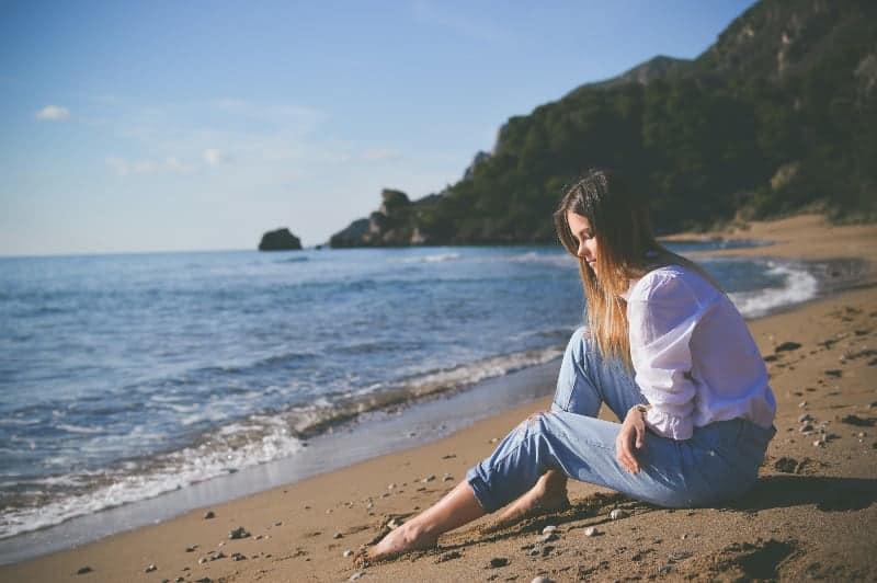 Frau die am Strandufer während des Tages sitzt