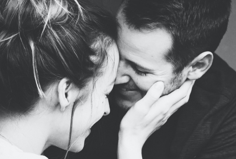 Graustufenfotografie der Frau, die das Gesicht des Mannes hält