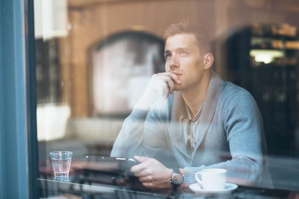 In der Bar am Fenster sitzt ein imaginärer Mann mit einer Tablette in der Hand