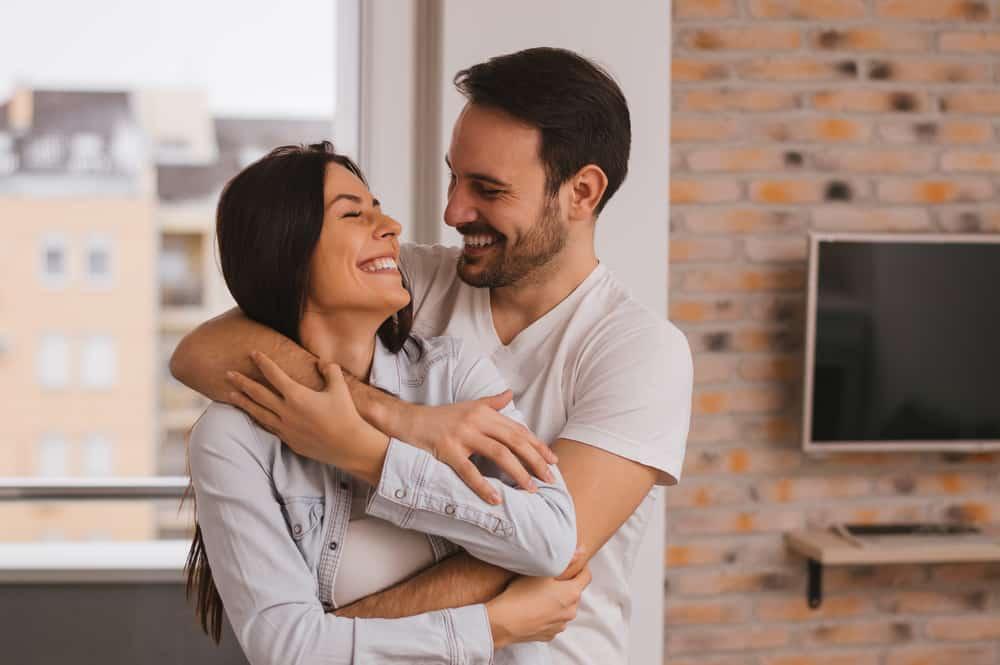 In der Wohnung steht in den Armen eines schönen lächelnden Liebespaares
