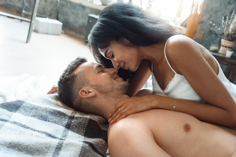 Mädchen küsst Freund im Bett
