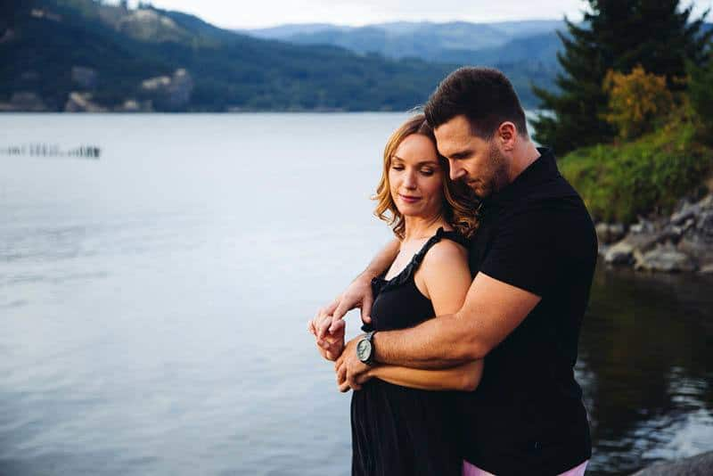 Mann umarmt Frau von hinten am See
