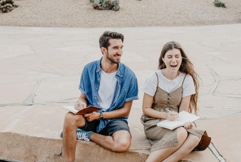 Mann und Frau sitzen nebeneinander und halten Notizbücher