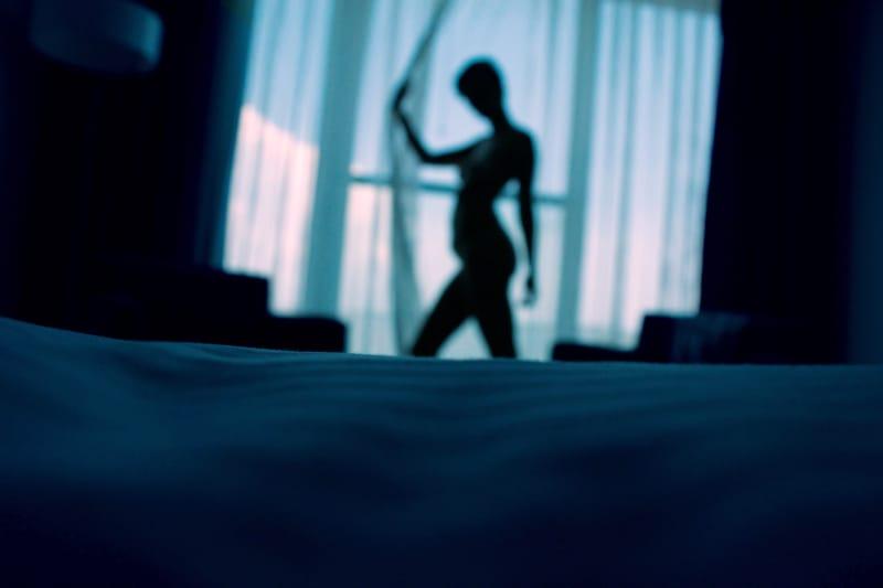 Schattenbildfoto der Frau, die neben Fenstervorhängen steht