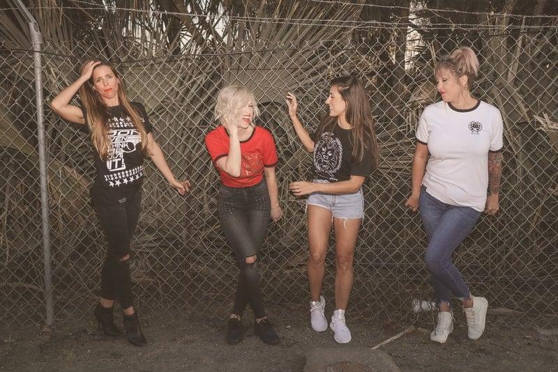 Vier lächelnde Frauen stehen an einem Weidenzaun