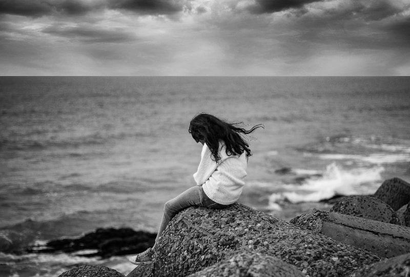 traurige Frau, die allein am Meer sitzt