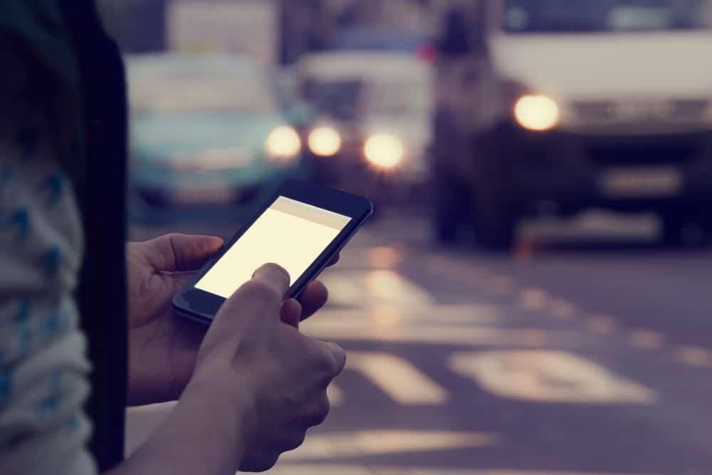 ein Handy in den Händen eines Mannes draußen