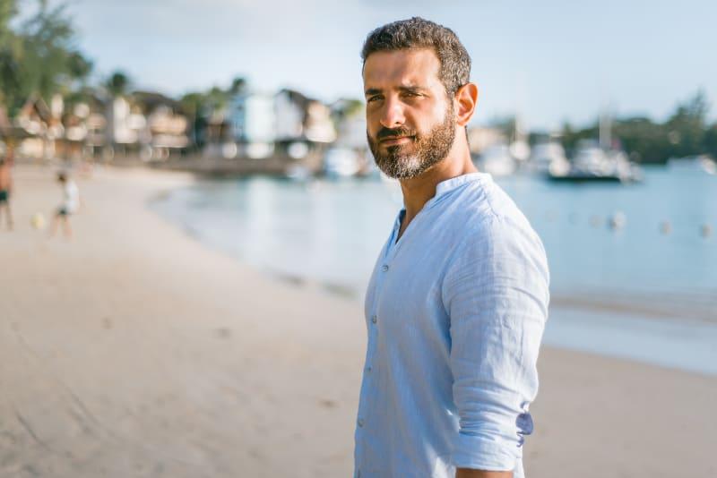 ein Mann in einem weißen Hemd am Strand