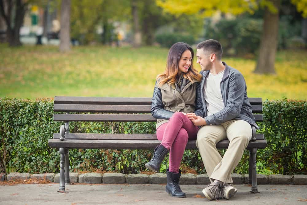 ein glückliches Liebespaar, das in einer Umarmung auf einer Parkbank sitzt
